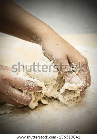 Woman's hands kneading dough to make bread.