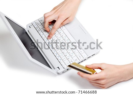 Woman's hands making on-line payment using laptop and credit card - stock photo