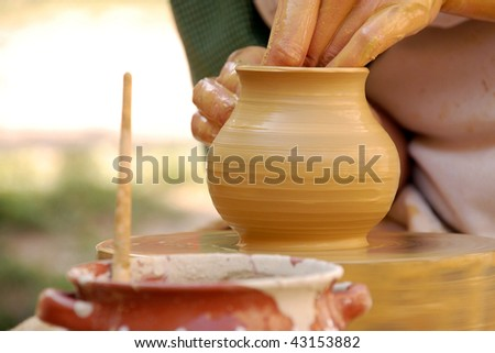 Woman's hands on a piece of pottery made of clay on a rotating wheel. - stock photo