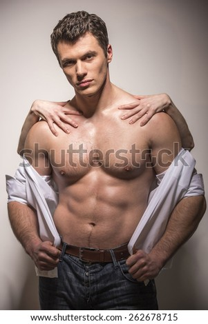 Woman's hands on a sexy man's torso on a white background.