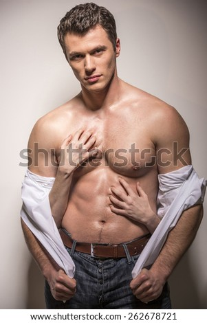 Woman's hands on a sexy man's torso on a white background. - stock photo