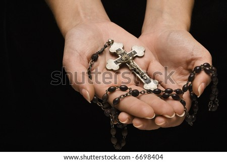 Woman's hands palm up cradling rosary with crucifix.