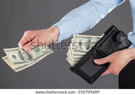 Woman's hands paying money on dark background