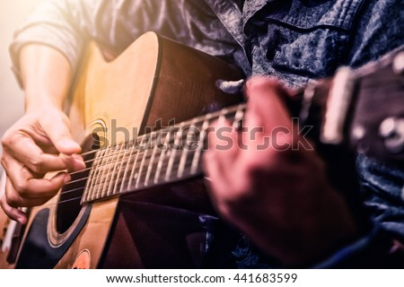 woman's hands playing acoustic guitar, close up - stock photo