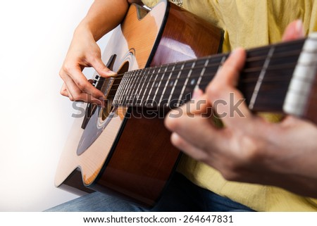 woman's hands playing guitar, close up - stock photo