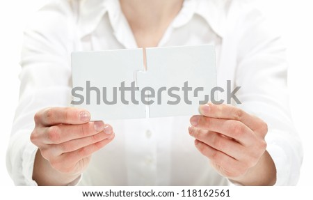 Woman's hands showing blank puzzles fitting each other - stock photo