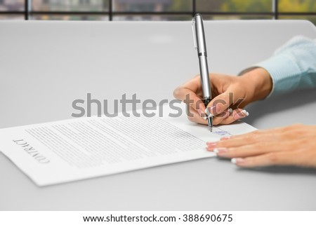 Woman's hands signing office papers. Close-up of secretary's daytime paperwork. One siganture makes many changes. Think before you sign. - stock photo