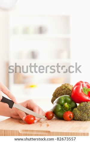 Woman's hands slicing tomatoes in a kitchen