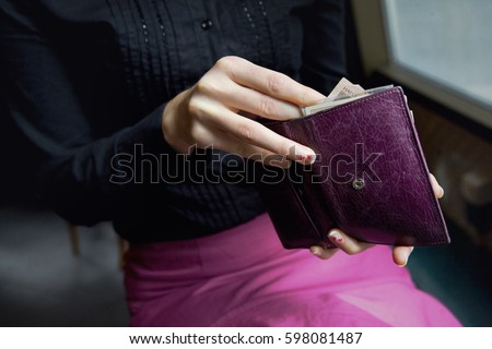 Woman's hands taking out money from a violet leather wallet.Woman's hands taking out money from a violet leather wallet.