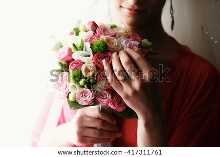 Woman's hands touch a pink wedding bouquet