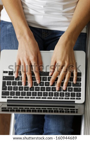 Woman's hands typing on a modern laptop computer - stock photo