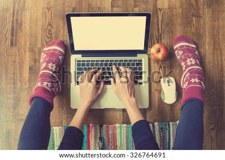 Woman's hands typing on laptop keyboard. Study and work online, freelance, warm socks, winter, home comfort and relax - stock photo