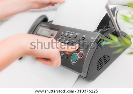 Woman's hands using fax - stock photo
