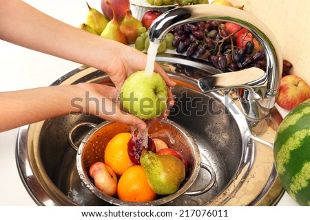 Woman's hands washing apple and other fruits in colander in sink - stock photo