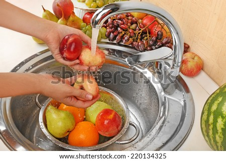 Woman's hands washing peaches and other fruits in colander in sink - stock photo
