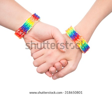 woman's hands with a bracelet patterned as the rainbow flag