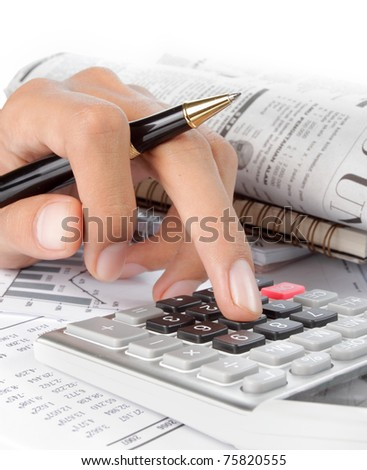 woman's hands with a calculator and a pen. newspaper on a background