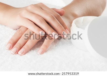 Woman's hands with cream on white towel, close-up. - stock photo