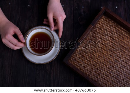 woman's hands with cup of tea and rattan tray, dark tones