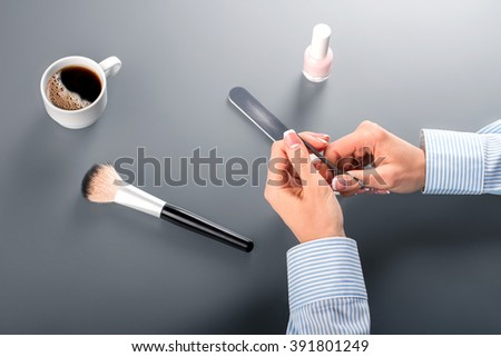Woman's hands with manicure scissors. Businesswoman using manicure scissors. Careful with the sharp metal. And now the scissors. - stock photo
