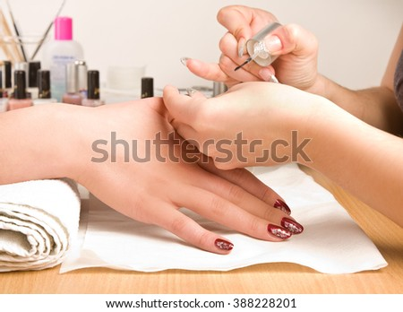 Woman's hands with nail brush drawing on nails - stock photo