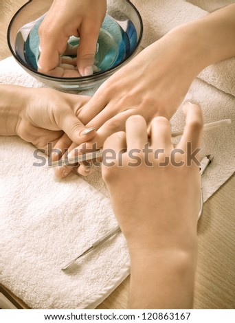 Woman's hands with nail file (retro styled)