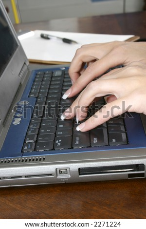 Woman's hands with typing on laptop computer keyboard.