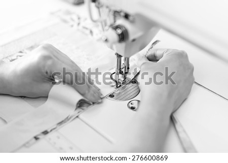 Woman's hands working on sewing machine. Black and white. - stock photo