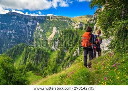 Woman's hiking team with colorful backpacks walking on narrow trail,Bucegi mountains,Carpathians,Transylvania,Romania,Europe - stock photo