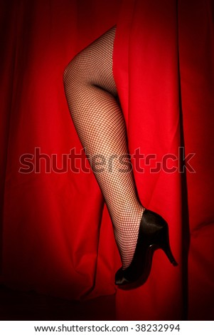 Woman's leg through red stage curtain - stock photo