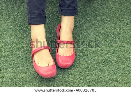 Woman's leg wearing a pair of red-pink fashion shoes and sitting on a green grass.