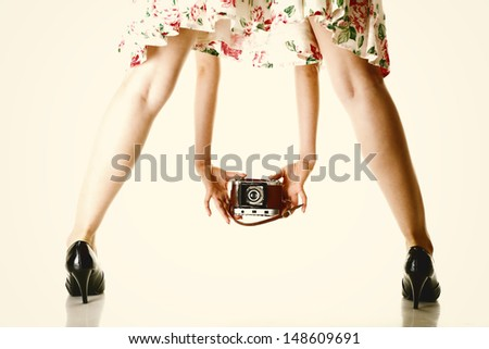 woman's legs and hand girl taking picture using vintage camera white background - stock photo