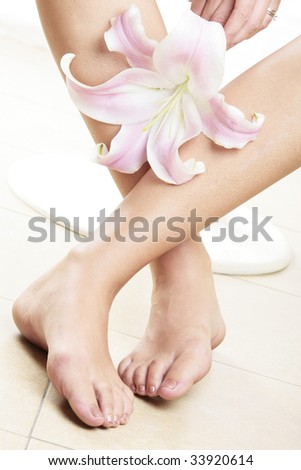 Woman's legs and pink lilly flower