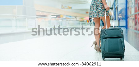Woman's legs and travel suitcase at international airport tax free shopping zone