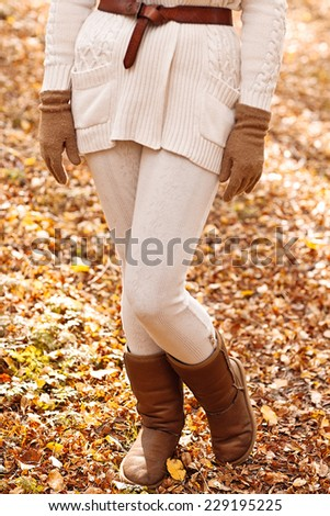 woman's legs in brown uggs in autumn forest - stock photo