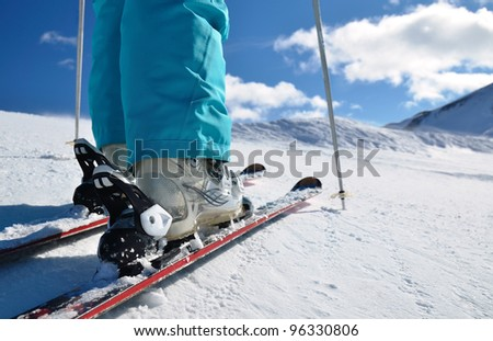 woman's legs in ski boots, standing on alpine skis - stock photo