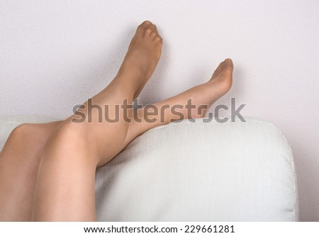 Woman's legs in tights on white sofa background