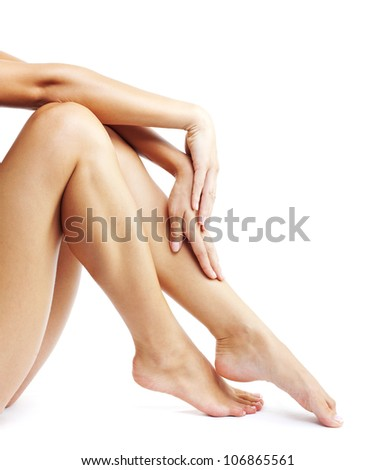Woman's legs isolated on white background, beautiful tanned  female feet and hands conceptual of spa, purity, pedicure, foot care, waxing depilation, epilation, healthy lifestyle, clean soft skin - stock photo