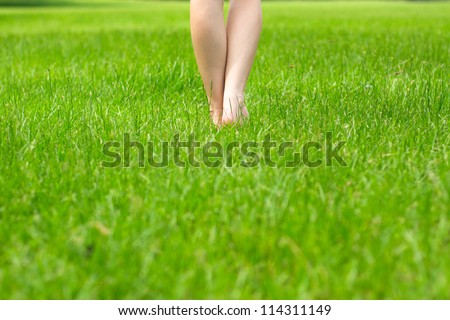 Woman's legs on fresh green grass