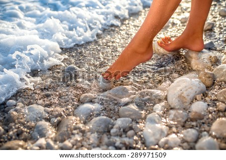Woman's legs on the stone beach with foam water on sunset - stock photo