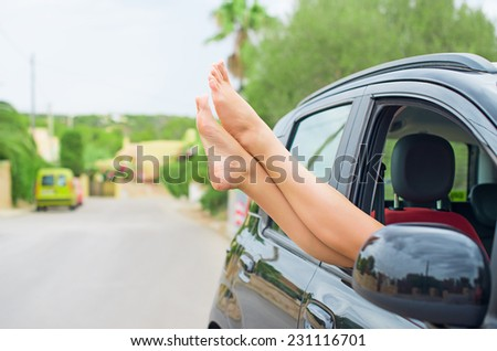 Woman's legs out of the car window.  - stock photo