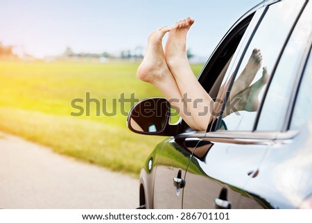 Woman's legs out of the car window.Concept of carefree funny trip. - stock photo