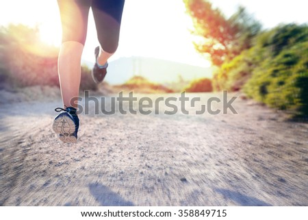 Woman's legs running outdoors at sunset hour - stock photo