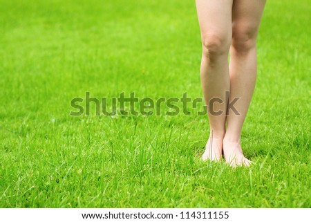 Woman's legs stand on fresh green grass - stock photo