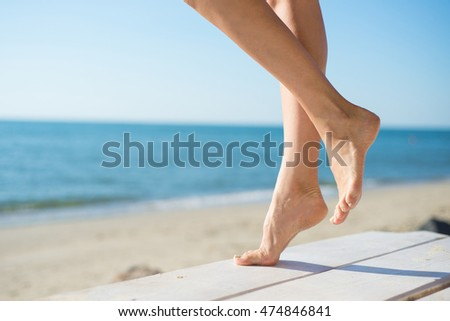 Woman's legs tanning on the beach