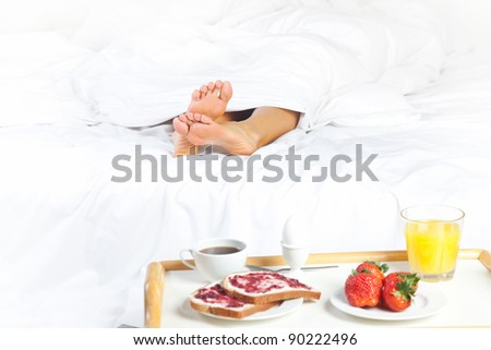 woman's legs under the blanket and breakfast near the bed - stock photo