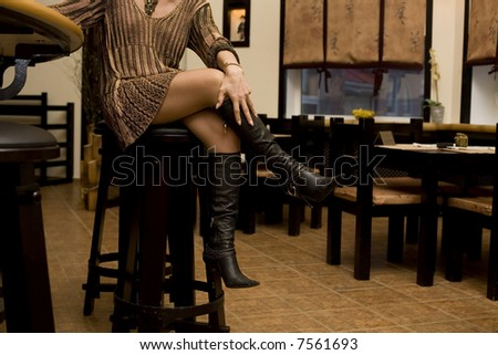 Woman's legs #2. Woman sitting in japanese bar - stock photo