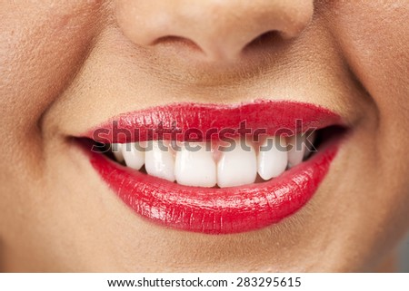 Woman's lips smiling showing her teeth. Wearing bright red lipstick