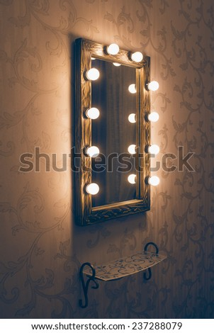 Woman's makeup place with mirror and empty shelf - stock photo