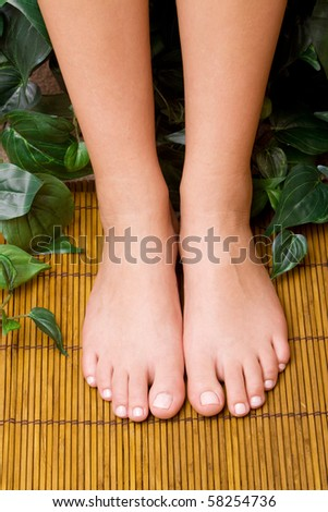 Woman's pedicured feet on bamboo mat - stock photo